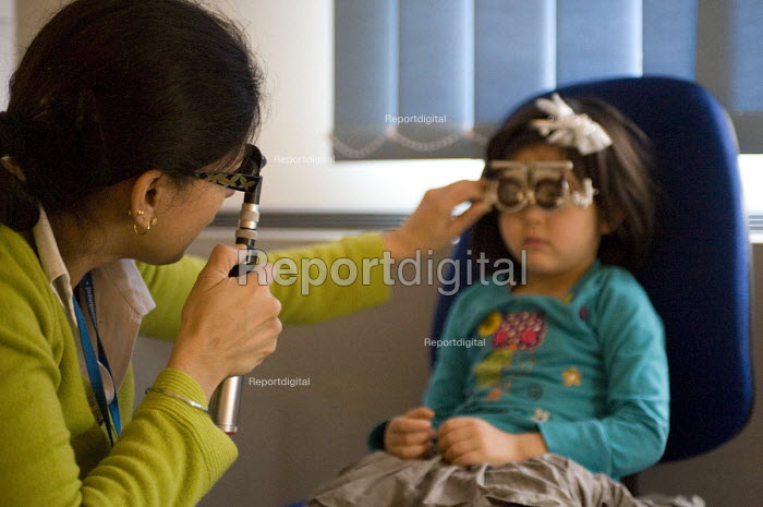 Consultant Optometrist checking a young girls eyes for astigmatism at the Birmingham NHS Paediatric Eye Service. - Timm Sonnenschein - 2012-01-10