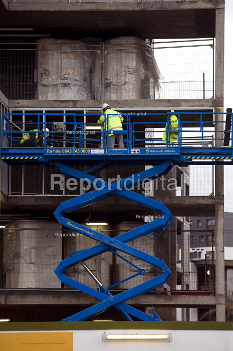 A worker on a hydraulic scissor lift. BAM contractors working at the Aston University development in Birmingham. - Timm Sonnenschein - 2012-01-18