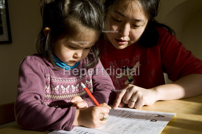 A girl practicing phonics for homework with the help of her mother, Birmingham. - Timm Sonnenschein - 2012-01-22