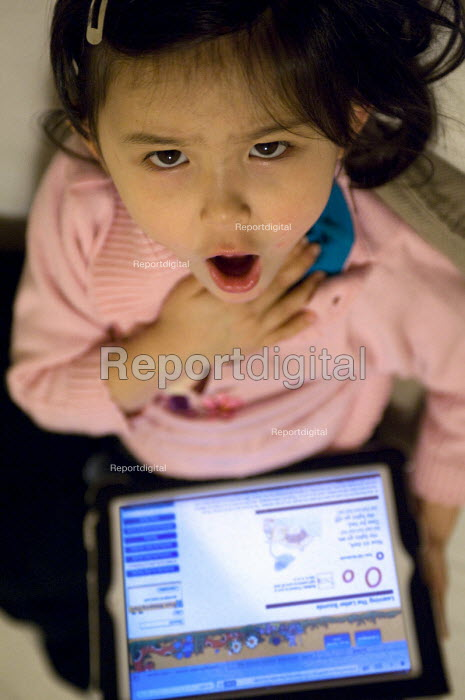 A girl practicing phonics singing along Jolly Songs using an IPad application at home. - Timm Sonnenschein - 2012-02-05