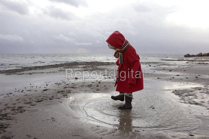 A girl playing in puddles and splashing about in the cold on beach, Baltic Sea, Germany - Timm Sonnenschein - 2011-12-29