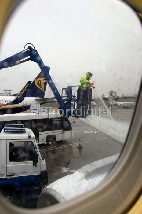 Through the porthole window Birmingham Airport ground staff de-icing the wings by spraying fluid onto a grounded Flybe plane prior to takeoff. The plane is delayed due to the need to remove freezing rain from the iced up wings prior to take-off - Timm Sonnenschein - 2012-02-10