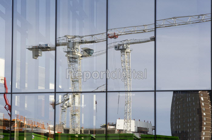 Construction site cranes reflected in the windows of a new Aston University building. Development is being undertaken by BAM Construction. - Timm Sonnenschein - 2012-03-29