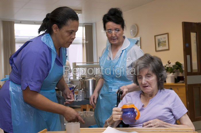 An NHS housekeeper and a rehabilitation assistant giving a drink to an elderly patient, Moseley Hall Hospital, Birmingham - Timm Sonnenschein - 2012-07-25
