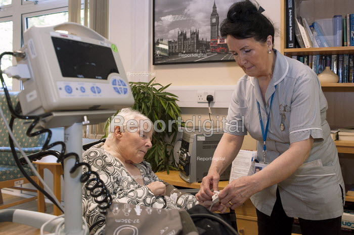 An NHS rehabilitation assistant measuring the blood pressure of an elderly patient, Moseley Hall Hospital, Birmingham - Timm Sonnenschein - 2012-07-25
