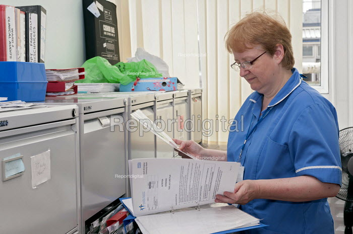 An NHS nurse checking the nutrition screening in a patients file, Moseley Hall Hospital, Birmingham - Timm Sonnenschein - 2012-07-25