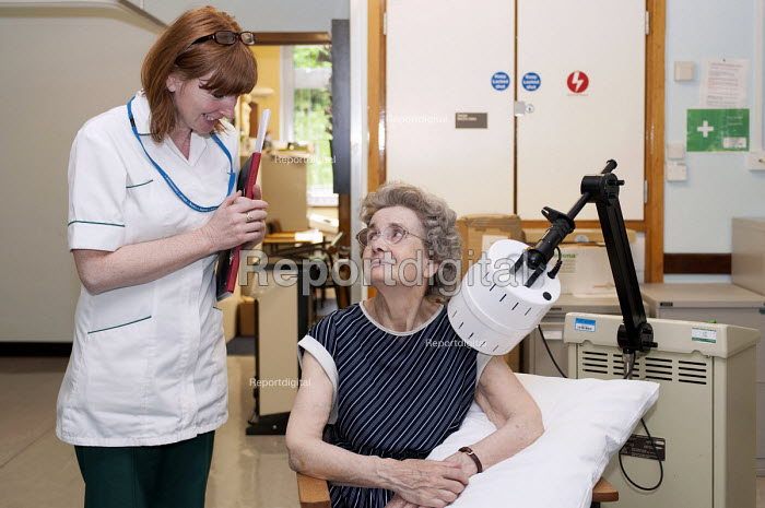 An NHS occupational therapist talking with an elderly patient that is receiving a shortwave treatment to her shoulder using an EMS Physio Megapulse II, Moseley Hall Hospital, Birmingham - Timm Sonnenschein - 2012-07-25