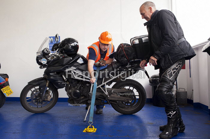 A P&O worker securing a Triumph Tiger 800 motorcycle to the deck aboard the Spirit of Britain cross-channel ferry before its departure from Dover to Calais - Timm Sonnenschein - 2012-07-28