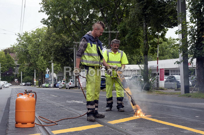 Road workers of the City of Essen burning off and removing temporary road markings during extensive roadworks, Germany - Timm Sonnenschein - 2012-07-31