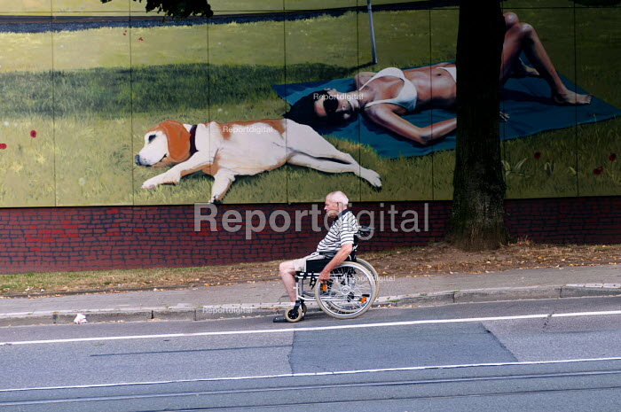 An old and disabled man in a wheelchair pushing himself down the road past a wallpainting of a , Essen, Germany - Timm Sonnenschein - 2012-08-21