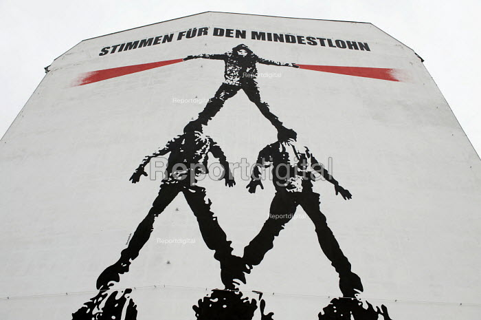 Stimmen fr den Mindeslohn, Vote for the minimum wage, Human pyramid by artist Victor Ash, Mural in Support of the proposal for a Statutory Minimum Wage, commissoned by Ver.di, the United Service Union of Germany. It is located in the front of The Reichstag building in BerlinBerlin Mitte, Germany - Timm Sonnenschein - 2012-08-31
