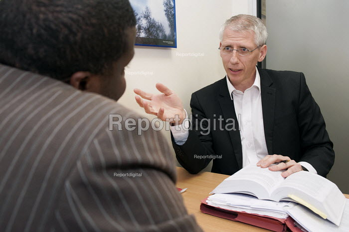 Specialist immigration solicitor Sean Mcloughlin of TRP Solicitors, Birmingham using the Immigration Law Handbook in advising an African client on his case under the legal aid scheme. - Timm Sonnenschein - 2012-10-08