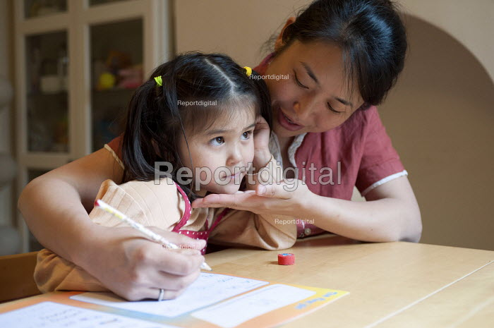 A year one schoolgirl practicing neat writing doing her homework with the help of her mother - Timm Sonnenschein - 2012-07-08