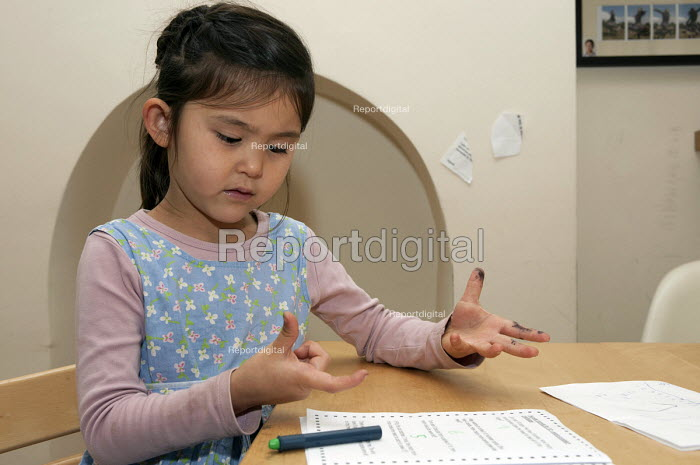 A year one schoolgirl counting with her hands doing her maths homework - Timm Sonnenschein - 2012-10-13