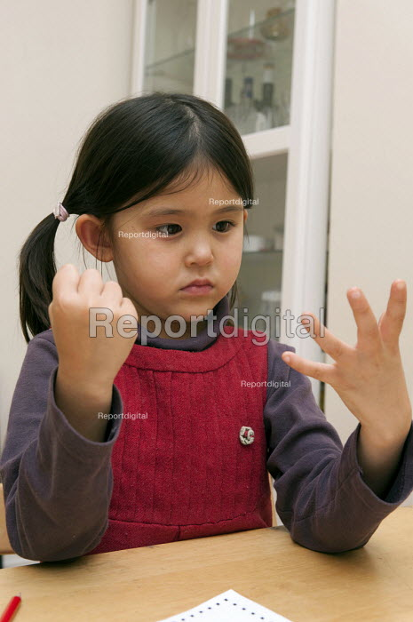 A year one schoolgirl counting with her hands doing her maths homework - Timm Sonnenschein - 2012-10-14