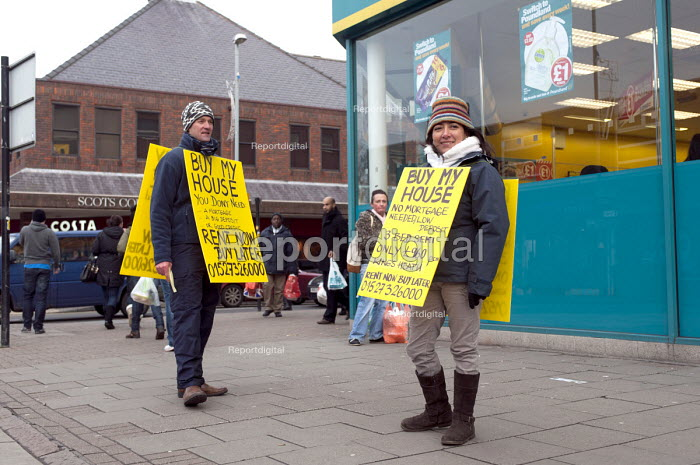 A couple wearing sandwich boards advertising the sale of their house and an option to rent now and then buy later. Selling direct to the public and avoiding estate agents fees, Kings Heath high street, Birmingham - Timm Sonnenschein - 2013-01-12