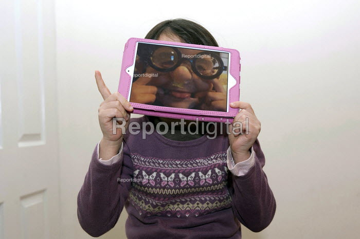 A girl hiding her face behind an iPad mini that shows a photograph of herself wearing funny glasses a false nose and making a face. - Timm Sonnenschein - 2013-01-27