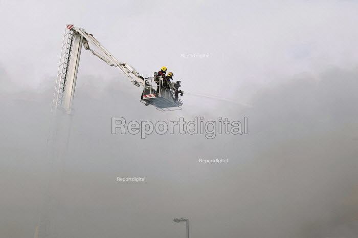 Firefighters spraying a jet of water from a hydraulic platform. West Midlands Firefighters attending a fire that broke out in a Cash Converters shop, suspected arson, Kings Heath, Birmingham - Timm Sonnenschein - 2013-03-27
