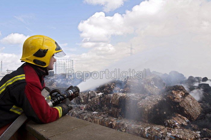 Firefighter spraying a jet of water. Fire and Rescue Service attending a fire at Smurfit Kappa paper recycling plant, Nechells, Birmingham - Timm Sonnenschein - 2013-04-18