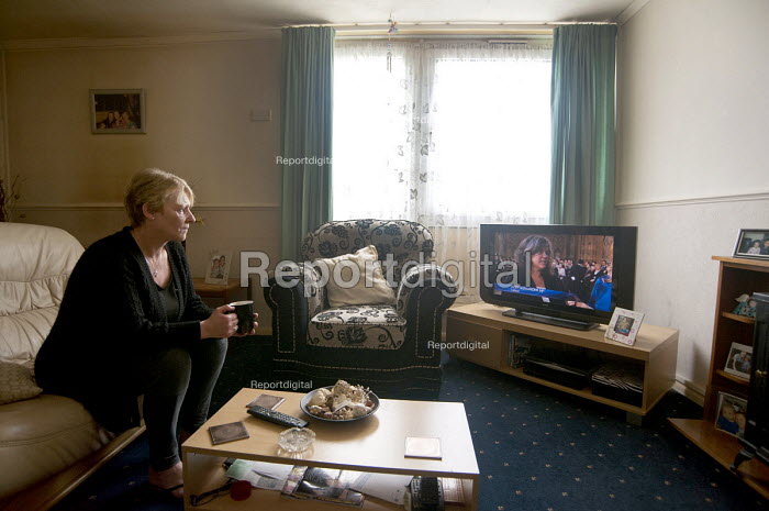 Kathleen, watching politicians on TV in her council flat in Ladywood, Birmingham. She was asked to pay bedroom tax for one room, which would take her into debt. She has lived in the flat for 13 years, first with her 3 daughters who now have moved out but come to visit and stay with her grandchildren. She works part time as a cleaner for the same employer for 19 years but is reliant on housing benefit. Ladywood has the highest number of people in Birmingham effected by the bedroom tax. - Timm Sonnenschein - 2013-05-08