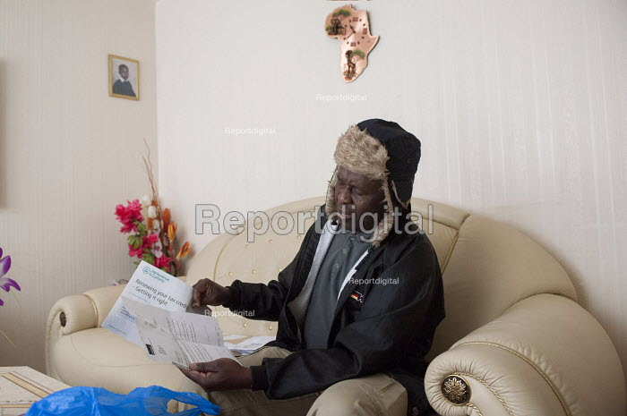 Thandi looking at paperwork regarding his council flat and benefits, Highgate, Birmingham. He was asked to pay bedroom tax for one room, which would take him into debt. He was attacked in 2005 with injuries to his head and neck leaving him in a coma. After he was released from hospital him and his family moved here from Redditch in 2006 to be closer to the Birmingham rehabilitation centre. He lives here with his wife, son and daughter with whom he moved to England from Zimbabwe in 2002. His daughter is now studying in Nottingham but still comes for visits and uses the room. - Timm Sonnenschein - 2013-05-30