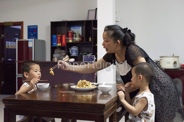 A mother helping her son and nephew with their dinner, De Qing, Moganshan, China - Timm Sonnenschein - 2013-08-16