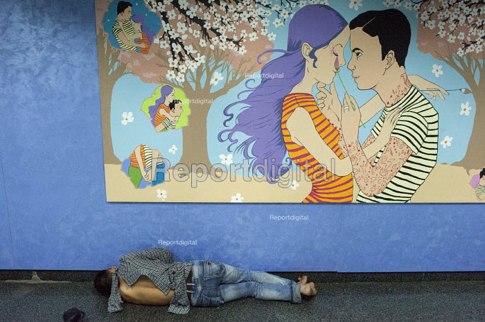 A homeless man sleeping below an artwork by Shannon Toth, a Nippon Paint comissoned illustration - in the name of love Refresh Life, 2013 Metro painted artwork showing a happy couple in love, tube station, Shanghai, China - Timm Sonnenschein - 2013-08-22