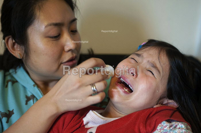 A mother attending to her crying child with a damp tissue after she hurt her jaw. - Timm Sonnenschein - 2013-10-23