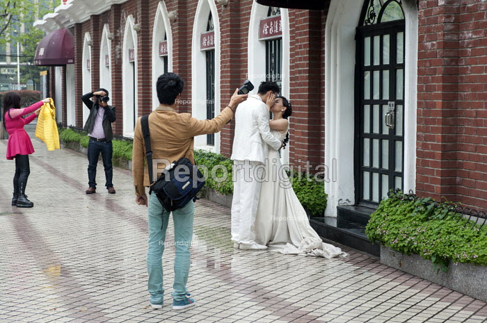 A wedding photographer and his assistants taking wedding photographs of a kissing couple in front of a historic facade purpose built for such photo shoots, Shanghai, China - Timm Sonnenschein - 2014-04-12