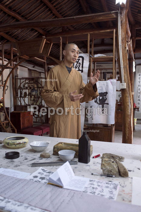 Young Buddhist monk explaining Chinese calligraphy, Tong Shan Temple, Moganshan, China - Timm Sonnenschein - 2014-04-15
