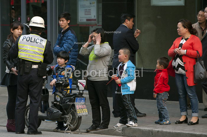 Police officer taking notes from eyewitnesses regarding an accident as bystanders gather around him, Shanghai, China - Timm Sonnenschein - 2014-04-08