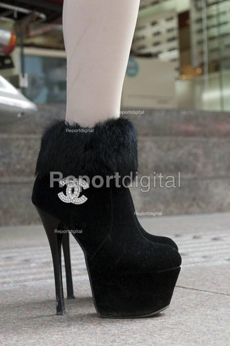 A woman wearing fake Chanel stiletto shoes, Nanjing Road, Shanghai, China - Timm Sonnenschein - 2014-04-09