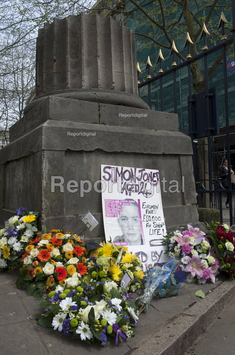 Placard mourning the death of Simon Jones at Euromin. Floral wreaths commemorating deaths at work and injured workers. The pillar is a memorial stone for workers that died during the construction of Birmingham Town Hall in 1833. Workers' Memorial Day, St Philips Cathedral Grounds, Birmingham. - Timm Sonnenschein - 2014-04-28