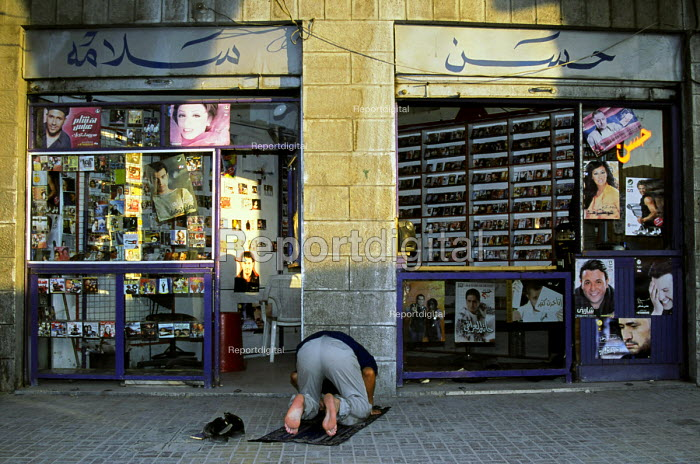 A Jordanian man prays in front of his video store on King Talal Street in the downtown area of the capital, Amman. Jordan,2004 - Steven Langdon - 2004-03-01