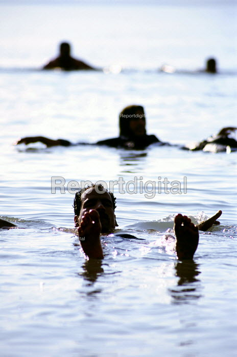 Local people float in the salty waters of the Dead Seas east bank, Jordan, the lowest point on the planet. - Steven Langdon - 2004-03-01