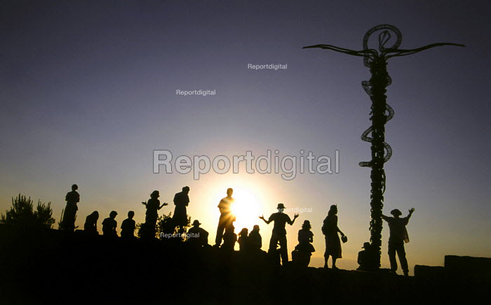 Tourists embrace the sunset over Promised land at Mount Nebos monastery next to the Serpentine Cross (The Brazen Serpent Monument) by Giovanni Fantoni, Jordan - Steven Langdon - 2004-03-01