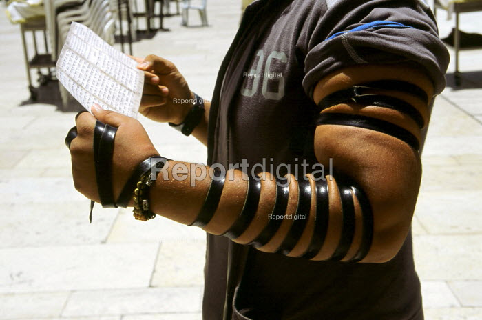 An Orthodox Jew man reads extracts from the Tenach and his arm wrapped in a tefillah during prayer at the wailing wall also known as the wailing wall - in the Old City. Jerusalem, Israel, 2005 - Steven Langdon - 2005-10-28