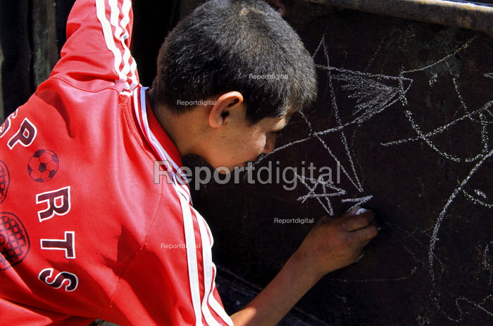 A young Palestinian boy draws stars on chunks of metal that have been left after the construction of the security wall which separates people in the Abu Dis area of East Jerusalem. Israel, 2005 - Steven Langdon - 2005-10-30