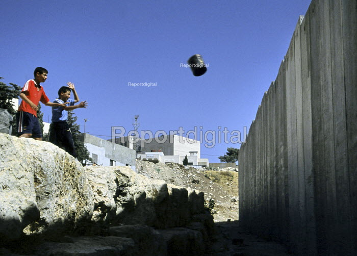 Palestinian children throw rubbish at the Israeli security wall near their homes in the Abu Dis area of East Jerusalem. The West Bank, 2005 - Steven Langdon - 2005-10-30