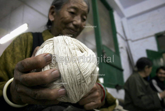 An elderly tibetan woman working in the wool rolling room of a carpet factory in Dharamsala, Kangra District. With age , many tibetan women after years of weaving carpets have now been given easier tasks because of their health and sight. In exile from Tibet. - Tashi Tobgyal - 2007-10-11