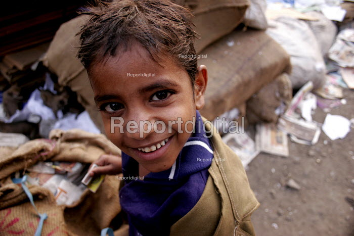 A young child scavenges through a garbage dump picking scrap for sale, New Delhi, India. - Tashi Tobgyal - 2007-12-07
