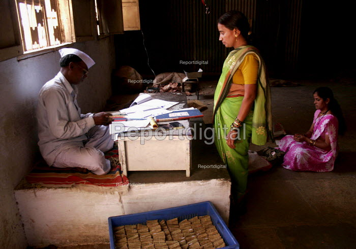 A woman gets paid her daily wage for rolling tobbaco. Women roll beedis (tendu rolled tobacco cigarettes) in Nasik, Maaharashtra. India. The Beedi industry is one of the largest in India - Tashi Tobgyal - 2009-05-26