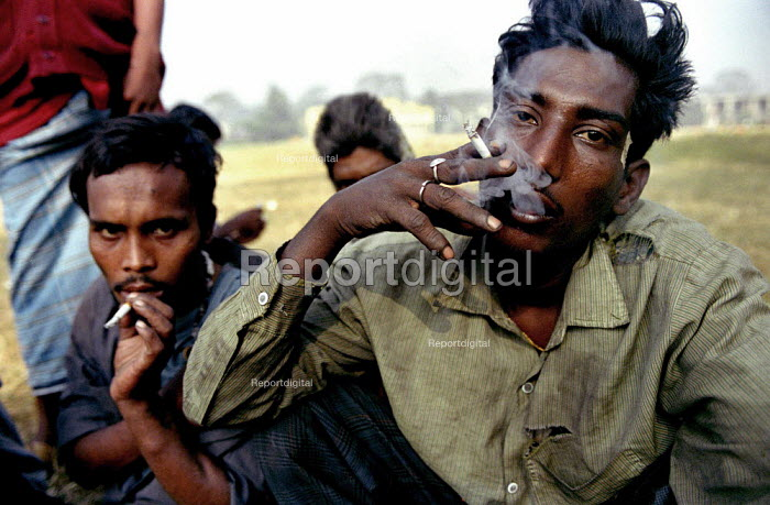 Bangladeshi men smoking cigarettes after injecting heroin in a park in Dhaka, Bangladesh 2002 - Thomas Morley - 2002-03-12