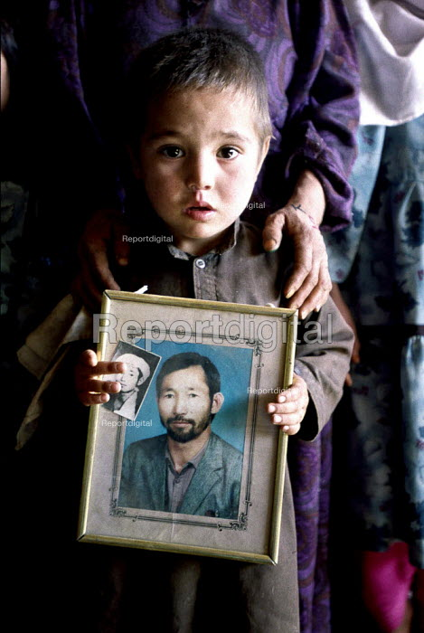 Afghan boy holds a photograph of his father killed in the Afghan civil war, whose mother now widowed has five children to look after. Kabul, Afghanistan 2002 - Thomas Morley - 2002-03-05