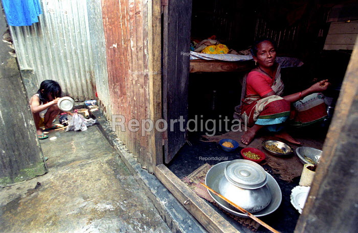 A brothel in Tangail, Bangladesh. A sex worker prepares food in her one room tin shed while her five year old daughter washes up. Tangail has over 700 sex workers expands at a rate of over twenty women a week. Tangail, Bangladesh 2002 - Thomas Morley - 2002-03-05