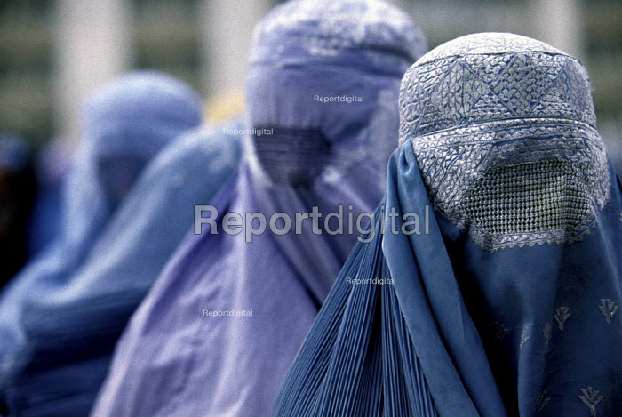 Afghan women wearing the traditional burka at a support centre for women who have been widowed by the Afghan civil war. The centre offers them food rations on a monthly basis. Kabul , Afghanistan 2002 - Thomas Morley - 2002-03-05