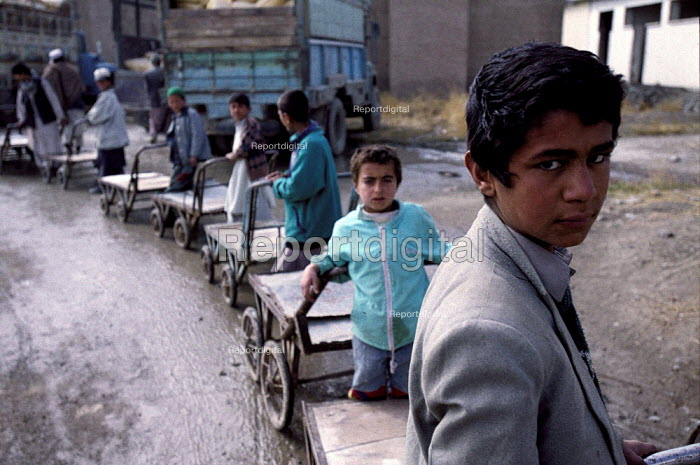 Young Afghan boys with barrows for food distribution at a centre for Afghan women who have been widowed by the Afghan civil war. The centre offers them food rations on a monthly basis. Kabul , Afghanistan 2002 - Thomas Morley - 2002-03-05