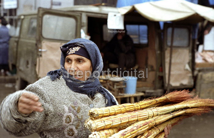 An Abkhazian woman sells brooms in the Abkhaz market, Tbilisi Georgia. The market is run by the Abkhazian Georgian refugees and has at times been a place of tension between them and indigenous Georgians. More than 350,000 refugees were created as a result of the conflict when Abkhazia tried to gain independence from Georgia. Georgia 2003 - Thomas Morley - 2003-03-05