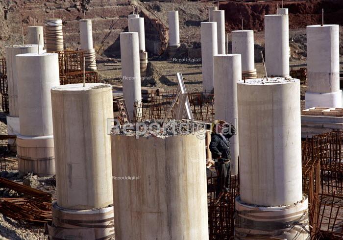 Construction worker amongst foundation columns on construction site - Len Grant - 2001-09-03