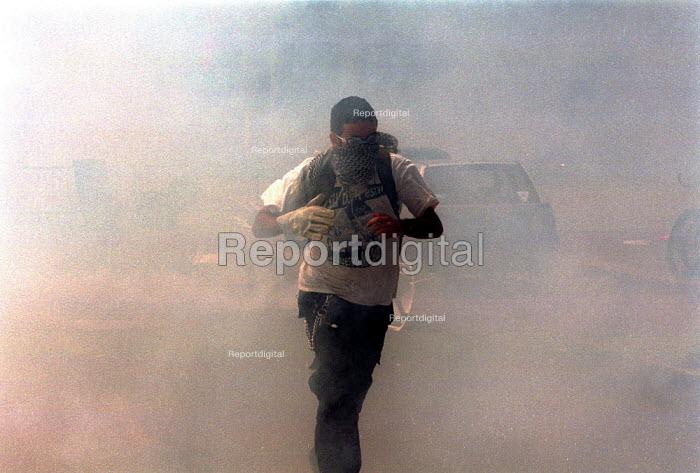 Anti Capitalist protest running through tear gas, Genoa G8 summit. - Paul Mattsson - 2001-07-21